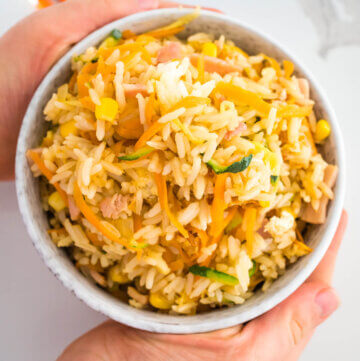 fried rice in a bowl with hands around it