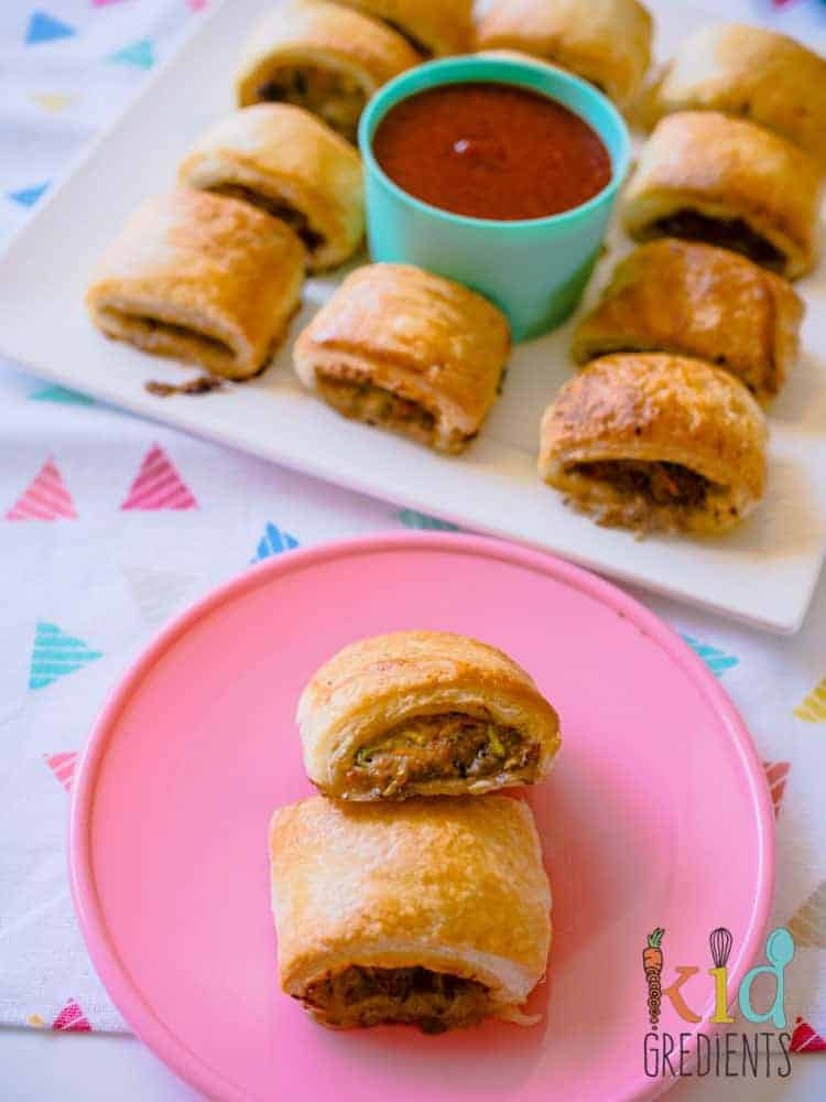 Sausage rolls ready to eat on a platter with two on a small party sized plate.