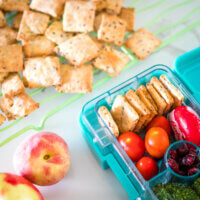 crunchy 5 ingredient cheese crackers in a lunchbox and on a wire rack
