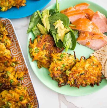 zucchini, carrot and pea fritters on a plate with salad