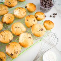 choc chip mini muffins, on a rack with a whisk and choc chips