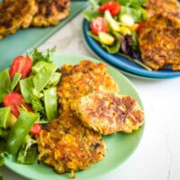 corn and zucchini fritters on a plate with a side salad