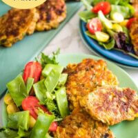 corn and zucchini fritters on a green plate with side salad