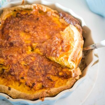 sweet potato, bacon and leek quiche, being taken out of the dish