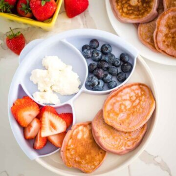raspberry ricotta pikelets on a plate with fresh strawberries and blueberries and ricotta