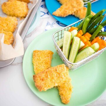 homemade fish fingers on a tray and on a plate with a basket of veggies