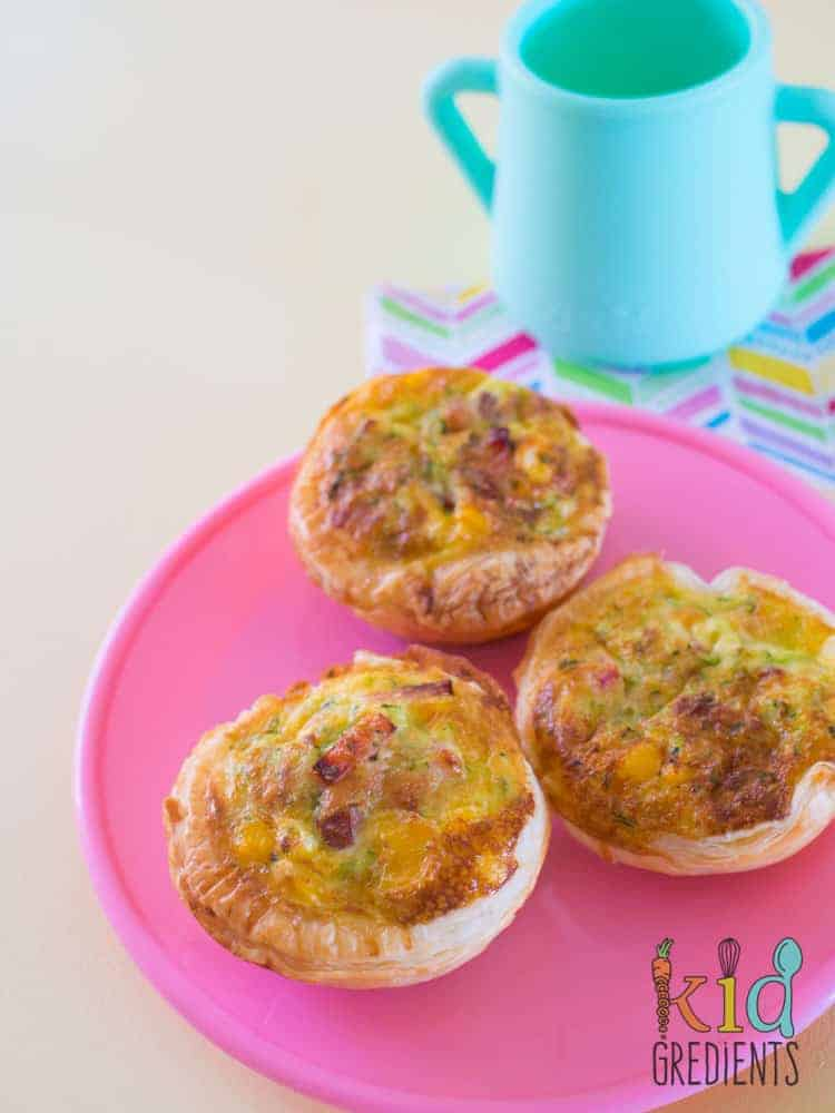 Lunchbox bacon and veggie quiches, three on a plate, portrait image