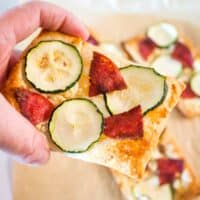 puff pastry pizza with salami and zucchini being held