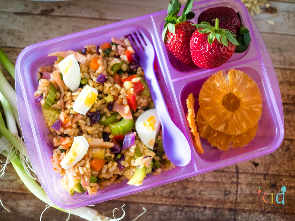 A plastic container filled with rice salad, dehydrated pineapple and strawberries