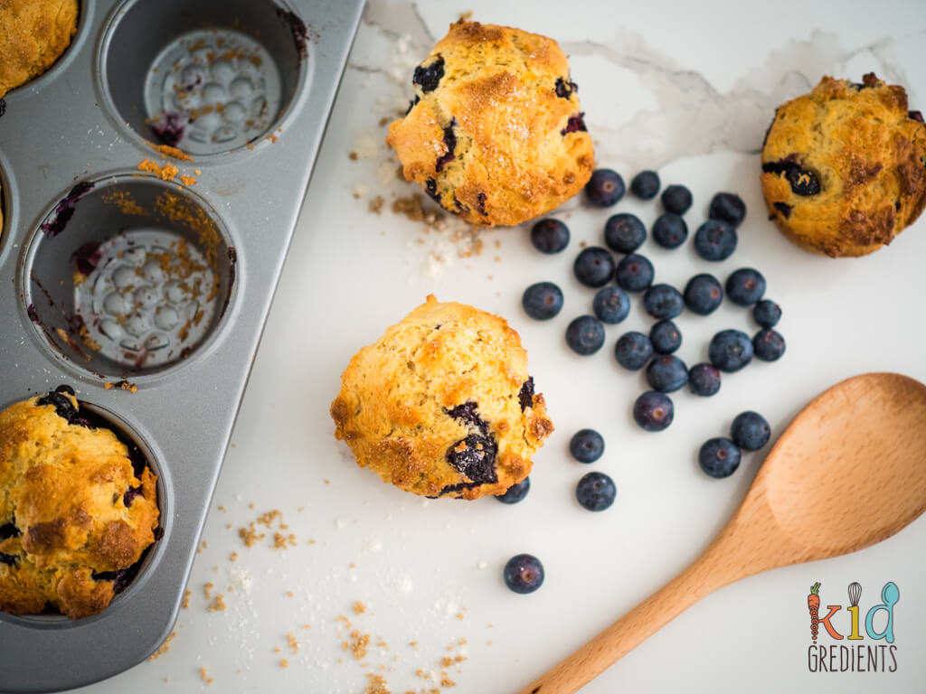 3 muffins sitting on the bench surrounded by blueberries and a spoon