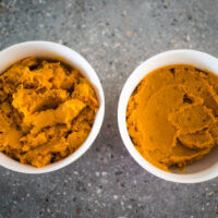 two dishes of pumpkin puree, one mashed and one food processed.