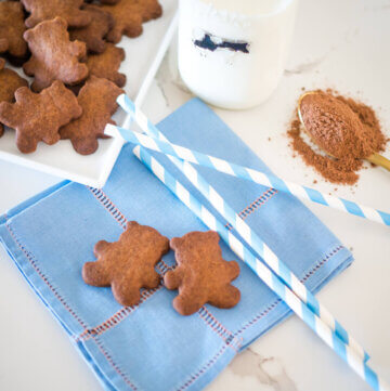 teddies on a napkin with straws, milk and a spoon of milo