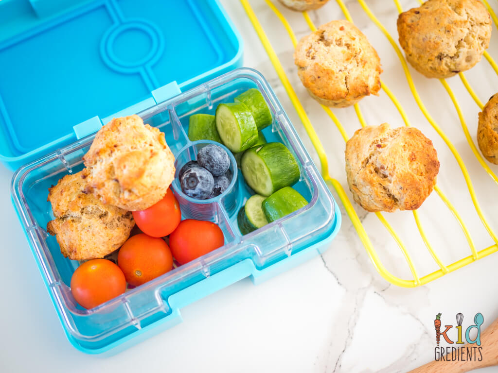 date and banana muffins in a snack box with cherry tomatoes, cucumbers and blueberries, extra muffins on a wire rack