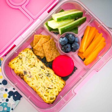 easy zucchini slice in a yumbox lunchbox with veggies and crackers