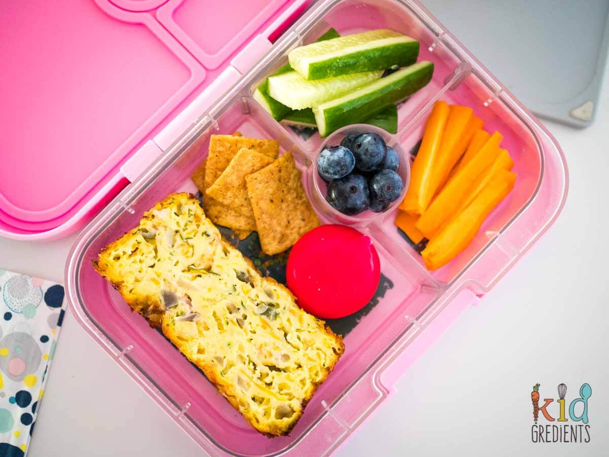 Easy zucchini slice in a yumbox with veggies and cheese and  crackers