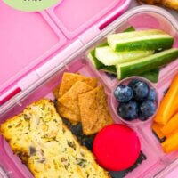 easy zucchini slice in a lunchbox with cheese and crackers and veggies