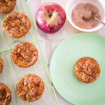apple zucchini muffins on a plate and cooling rack