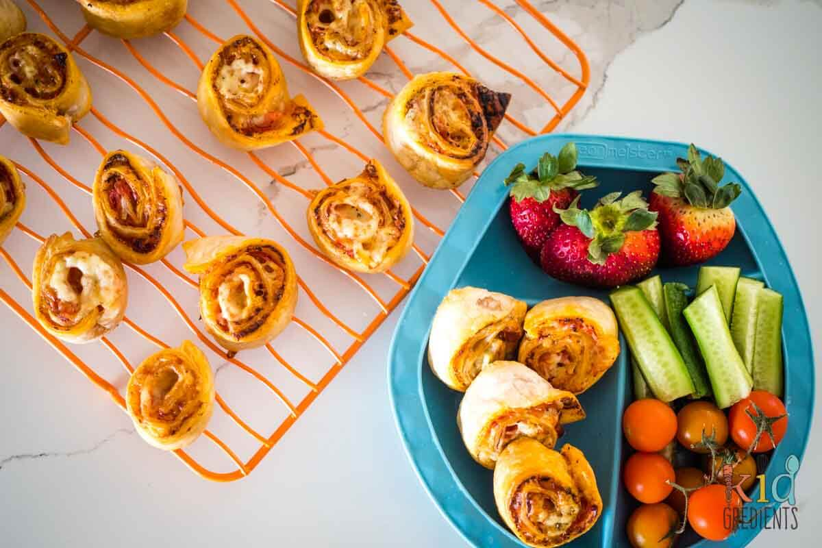 ham and cheese pizza scrolls on a plate with veggies and fruit and on a cooling rack