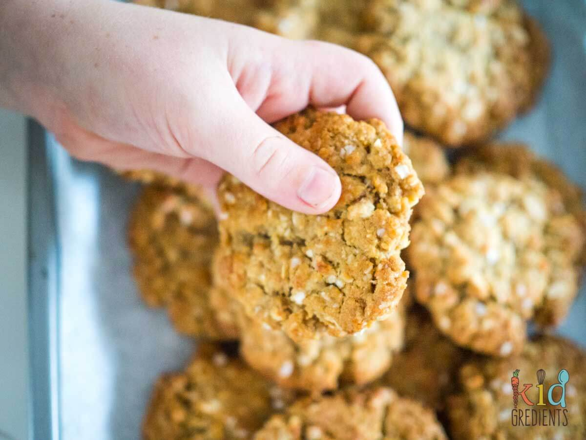 Kids hand holding healthy-ish anzac biscuits