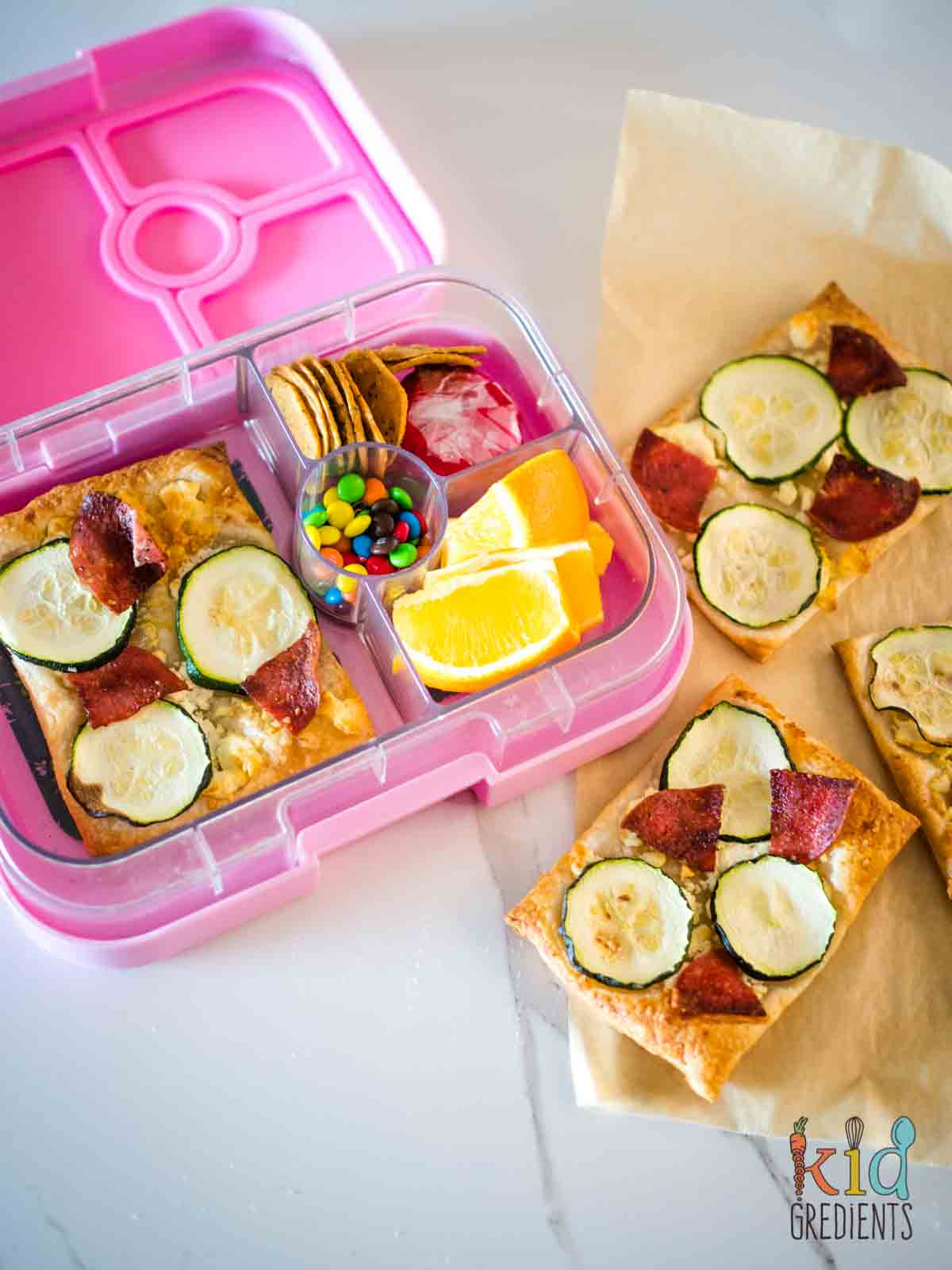 Puff pastry pizzas, on baking paper and in the lunchbox
