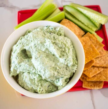 creamy spinach and fetta dip on a plate with crackers and cucumber